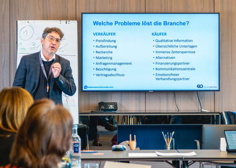 Georg Ortner erklärt vor einem Fernseher mit einer Präsentation, welche Probleme die Branche löst.